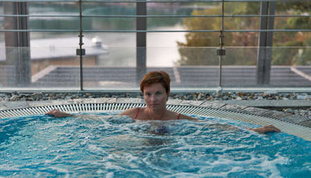 Middle aged Caucasian woman relaxing in jacuzzi with big window Редакционное
