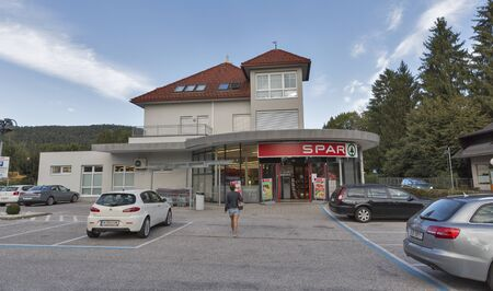 spar: VELDEN, AUSTRIA - SEPTEMBER 08, 2015: Unrecognized woman goes along the parking lot in SPAR supermarket. It is a Dutch multinational retail chain and franchise with 12,500 stores in 35 countries.