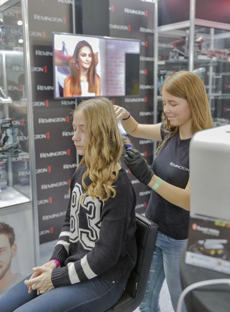 expositor: KIEV, UKRAINE - OCTOBER 11, 2015: Hairdresser makes hairstyle on Remington booth, personal care corporation, during CEE 2015, largest electronics trade show of Ukraine in ExpoPlaza Exhibition Center.