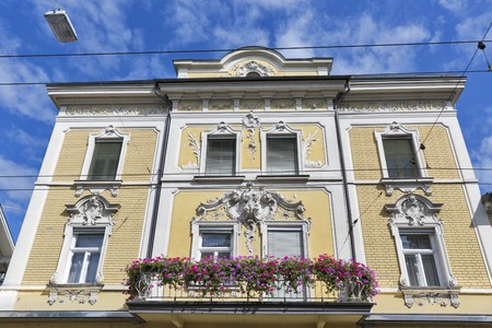 old building facade: Salzburg city old building facade with balcony, flowers and bas relief. Austria