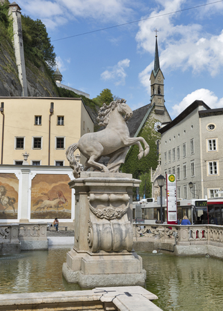 unrecognized: SALZBURG, AUSTRIA - SEPTEMBER 09, 2015: Unrecognized pedestrians near Horse Well  with a horse sculpture Editorial
