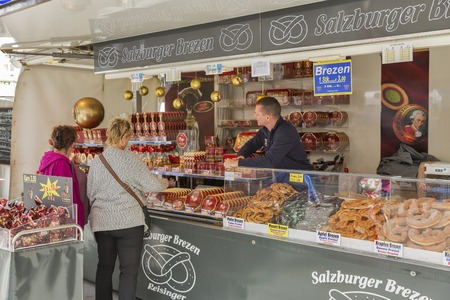 amadeus: SALZBURG, AUSTRIA - SEPTEMBER 09, 2015: Unrecognized people and seller in one of the numerous outdoor Mozart traditional sweets street market stall with Salzburger Brezen pretzel. Editorial