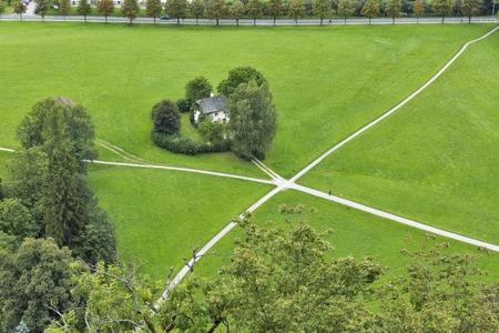 xanadu: House standing on the crossroad in the field. Salzburg suburb, Austria. Stock Photo