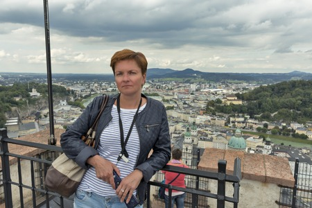 tourist guide: Caucasian middle aged tanned woman with electronic mobile audio tourist guide in hands stands against aerial view over Salzburg historic city center in Austria Stock Photo