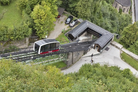 enables: SALZBURG, AUSTRIA - SEPTEMBER 09, 2015: People walk along a funicular cable car railway Festungsbahn. It enables visitors to reach the Hohensalzburg Fortress from the old town in less than a minute.