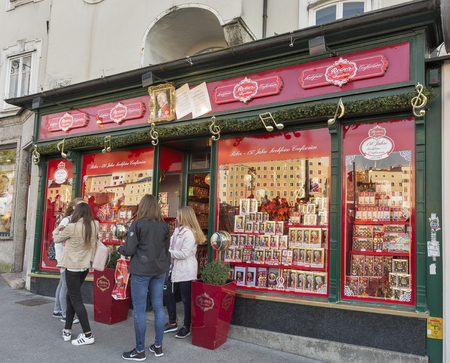 mozart: SALZBURG, AUSTRIA - SEPTEMBER 09, 2015: People in front of display of one of the numerous Mozart traditional sweets stores. World largest producer of Mozartkugeln is German company Reber Specialities.