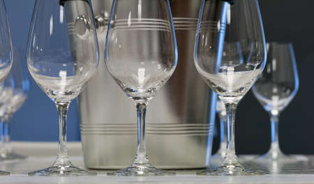 ice bucket: Empty wine glasses closeup in a row and ice bucket, focus on foreground