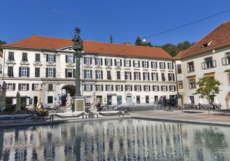 existed: GRAZ, AUSTRIA - SEPTEMBER 12, 2015: Karmeliterplatz with Holy Trinity column and pool with fountain in Old Town. The square was named after the former Carmelite convent which existed here until 1784. Editorial