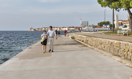 turistic: PIRAN, SLOVENIA - SEPTEMBER 16, 2015: Unrecognized people walk along waterfront. Piran is a medieval turistic town in southwestern Slovenia on the Adriatic Sea.