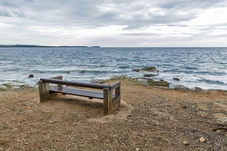 empty bench: Adriatic seascape with empty bench in Istria, Croatia Stock Photo
