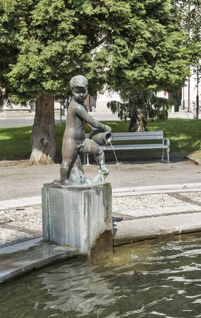 university fountain: Fountain with boy statue in front of University. Maribor, Slovenia Stock Photo