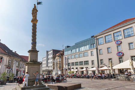 patron of europe: MARIBOR, SLOVENIA - SEPTEMBER 13, 2015: People have a rest in outdoor cafes near column topped by statue of St. Florian, patron of firefighters. Maribor is the second largest city in Slovenia.