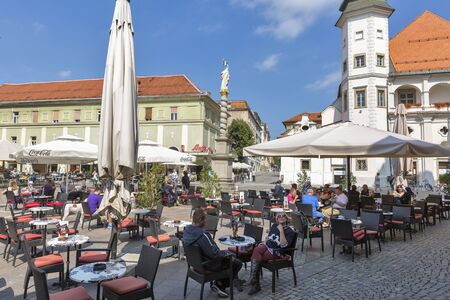 patron: MARIBOR, SLOVENIA - SEPTEMBER 13, 2015: People have a rest in outdoor cafes near column topped by statue of St. Florian, patron of firefighters. Maribor is the second largest city in Slovenia.