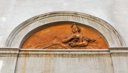 bas relief: Ancient bas relief of woman with flowers on building wall in Graz, Austria