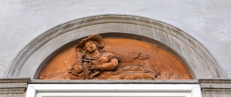 bas relief: Ancient bas relief of woman in a hat lies on building wall in Graz, Austria