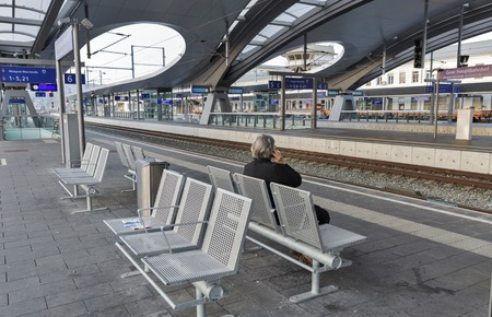 GRAZ, AUSTRIA - SEPTEMBER 12, 2015: Unrecognized senior woman on Graz Hauptbahnhof railway station platform. It serves as a major node on the Southern Railway which links it to Vienna and Slovenia. Editorial