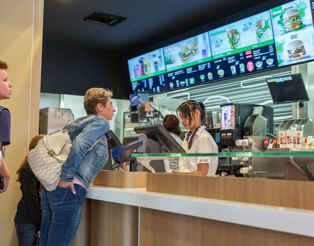 macdonald: GRAZ, AUSTRIA - SEPTEMBER 12, 2015: Unrecognized people make an order in McDonald restaurant. McDonald is the worlds largest chain of hamburger fast food restaurants founded in the United States. Editorial