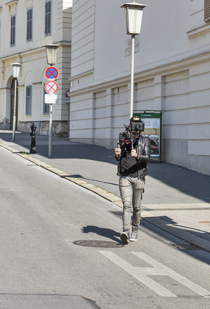 unrecognized: GRAZ, AUSTRIA - SEPTEMBER 12, 2015: Unrecognized cameraman getting video on Freiheitsplatz. Graz is the capital of federal state of Styria and second largest city in Austria.