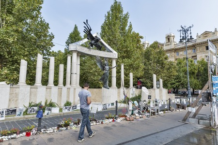 unrecognized: BUDAPEST, HUNGARY - SEPTEMBER 24, 2015: Unrecognized people walk along a memorial dedicated to the victims of Nazi Occupation during the Second World War.