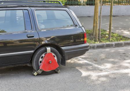 unpaid: Rear wheel lock on an unpaid parked car on city street