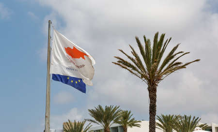 the european economic community: Flags of Cyprus and European Union on Paphos summer resort with palms Stock Photo
