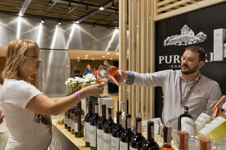 genuine good: KIEV, UKRAINE - June 04, 2016: Unrecognized people visit booth and taste Chateau Purcari wine from Moldova at Kyiv Wine Festival organized by Good Wine company in Parkovy Exhibition Center.