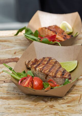 served: street food tuna and salmon steaks served with vegetables in carton plate closeup outdoor