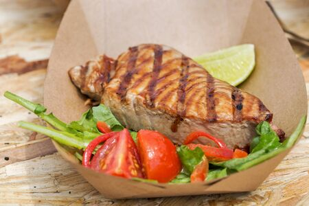 steak plate: street food tuna steak served with vegetables in carton plate closeup outdoor