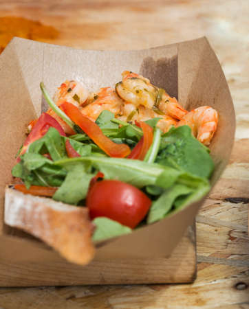 food plate: street food shrimps served with vegetables in carton plate closeup outdoor Stock Photo