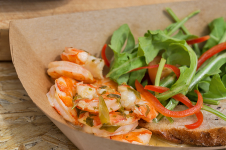 served: street food shrimps served with vegetables in carton plate closeup outdoor Stock Photo