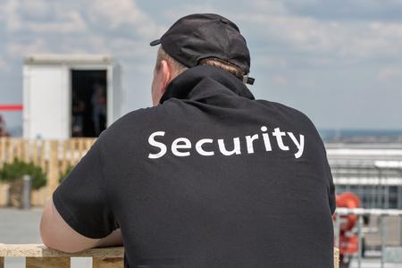 都市景観と屋外の義務に飽きてる認識されないセキュリティ ガード ゲイの身に着けている黒の t シャツ