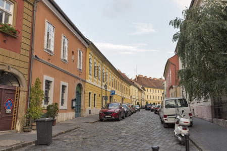 castle district: Old narrow street with parked cars in Budapest, Hungary. Buda Castle district.