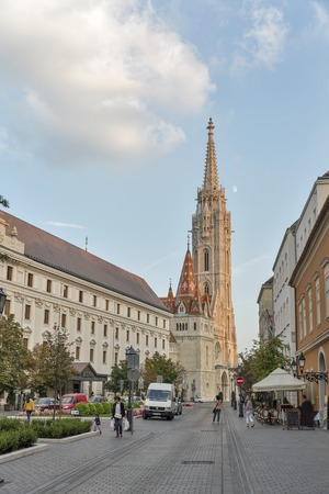 castle district: BUDAPEST, HUNGARY - SEPTEMBER 23, 2015: Unrecognized people walk in front of Hilton Hotel and Matthias church in castle district of Buda. Budapest is the capital and the largest city of Hungary.