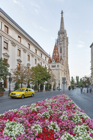 castle district: BUDAPEST, HUNGARY - SEPTEMBER 23, 2015: Unrecognized people walk in front of Hilton Hotel flowerbed and Matthias church in Buda castle district. Budapest is a capital and the largest city of Hungary.