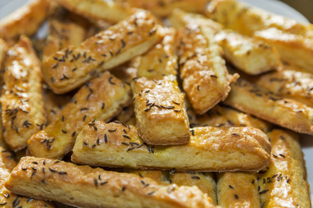 fresh baked puff cheese sticks with caraway seeds closeup