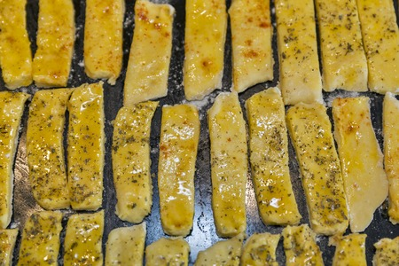 oven tray: raw dough salted cheese puff sticks with pepper and Provencal herbs closeup on oven tray