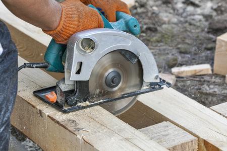 Carpenter working with circular saws closeup