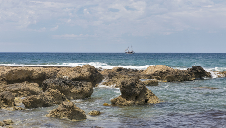 Seascape with sail ship and stones in Paphos, Cyprus.