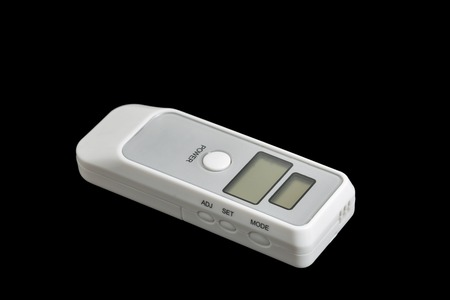 sobriety test: portable breath alcohol tester isolated on black background closeup