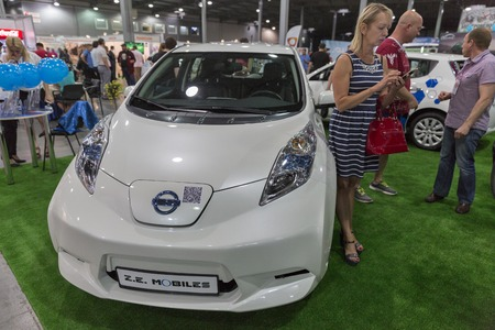 ze: KIEV, UKRAINE - JUNE 10, 2016: Visitors visit Z.E. Mobiles Eco Taxi company booth with Nissan Leaf electric hybrid car at 1st International Trade Show of Electric Vehicles Plug-In in KyivExpoPlaza.