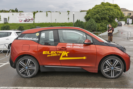 i3: KIEV, UKRAINE - JUNE 10, 2016: Visitors visit BMW i3 electric hybrid car parked outdoor on display at 1st International Trade Show of Electric Vehicles Plug-In in KyivExpoPlaza Exhibition Center. Editorial