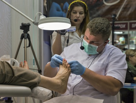 visitador medico: KIEV, UKRAINE - MARCH 25, 2016: Unrecognized man therapist demonstrates toenails treatment technology at 16th National Congress of Beauty Industry Estet Beauty Expo 2016 in IEC.