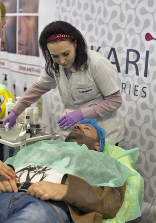 national congress: KIEV, UKRAINE - MARCH 25, 2016: Unrecognized cosmetology therapist demonstrates rejuvenation treatments on a middle age man at 16th National Congress of Beauty Industry Estet Beauty Expo 2016 in IEC. Editorial