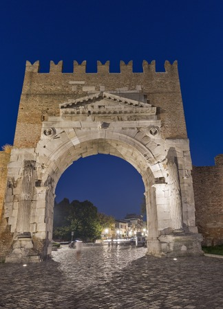 Arch of Augustus at night in Rimini, Italy. Ancient romanesque gate of the city - historical landmark, the most ancient roman arch that still stands intact. Stock Photo