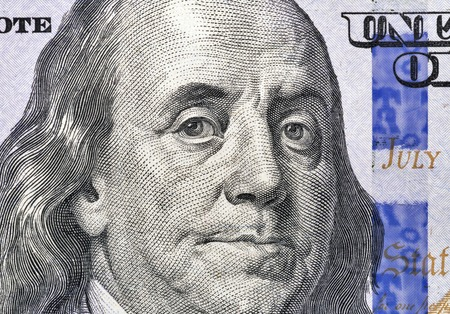 US President Benjamin Franklin portrait on one hundred dollar bill fragment macro