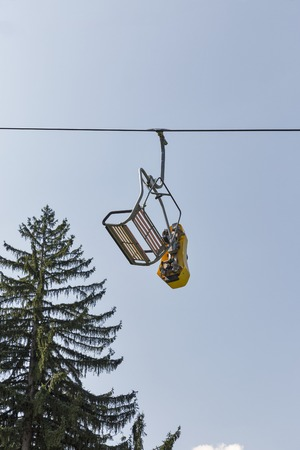chair on the lift: Ski chair lift carry summer toboggan sled against blue sky Stock Photo