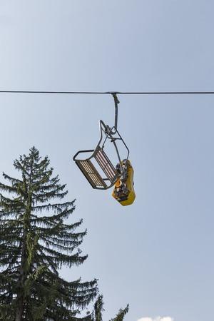 Ski chair lift carry summer toboggan sled against blue sky Stock Photo