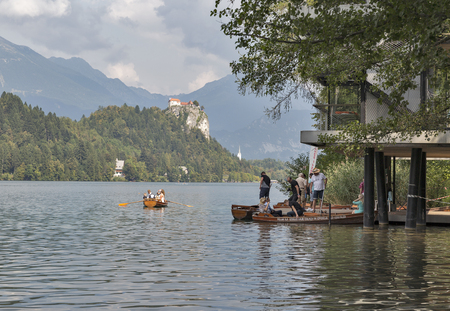 BLED, SLOVENIA - SEPTEMBER 10, 2016: Unrecognized people floating on boats on Lake Bled. Bled Lake is one of the picturesque sites of the nation.