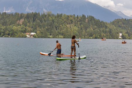 unrecognized: BLED, SLOVENIA - SEPTEMBER 10, 2016: Unrecognized people enjoying standup paddle boarding in a hot sunny day in the lake of Bled. Bled Lake is one of the picturesque sites of the nation.
