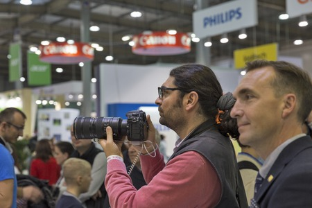 unrecognized: KIEV, UKRAINE - OCTOBER 09, 2016: Unrecognized visitors testing professional photographic cameras on Nikon booth during CEE 2016, the largest electronics trade show of Ukraine in KyivExpoPlaza EC.
